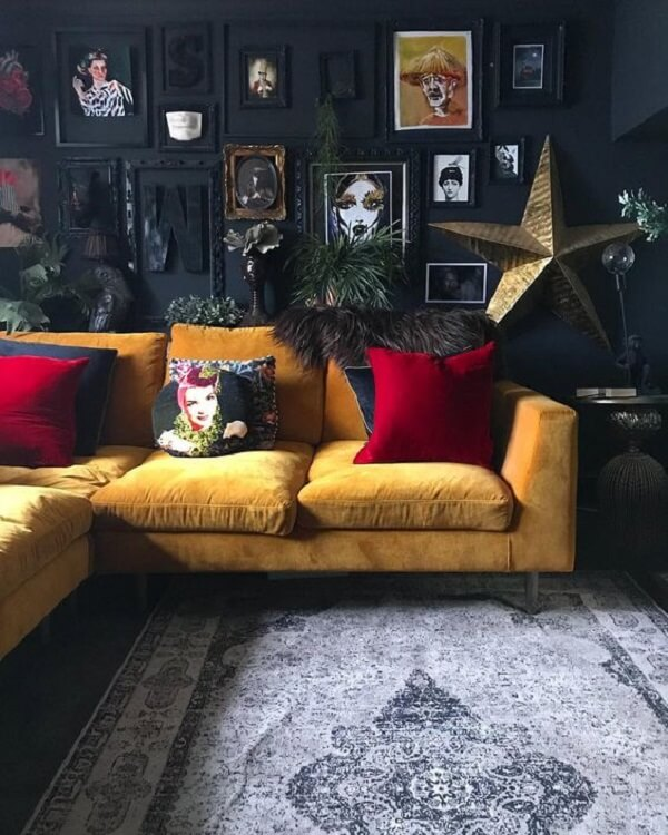 Ambiente dark com sofá amarelo e quadros decorativos