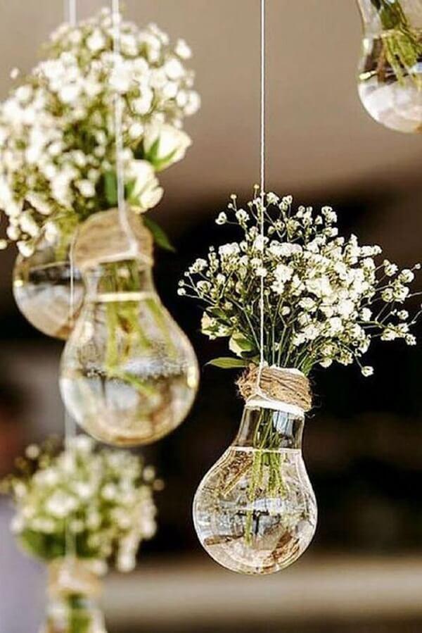 As lâmpadas penduradas servem de apoio para as flores mosquitinho