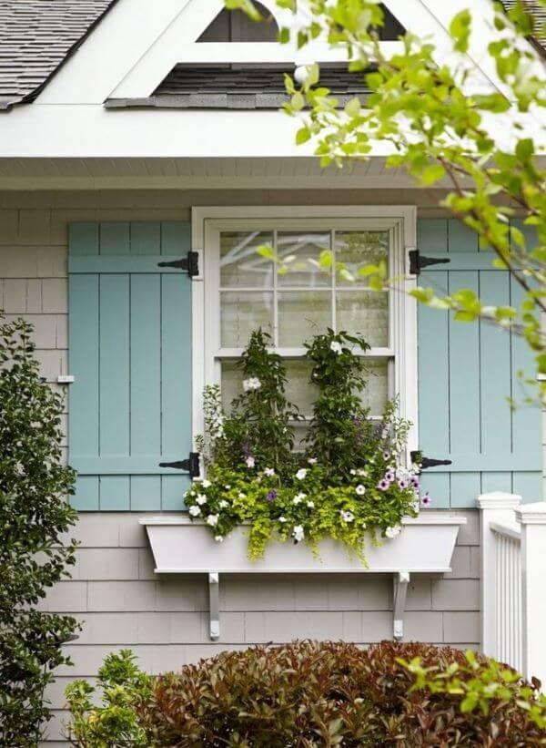 Floreira de madeira na janela de casa