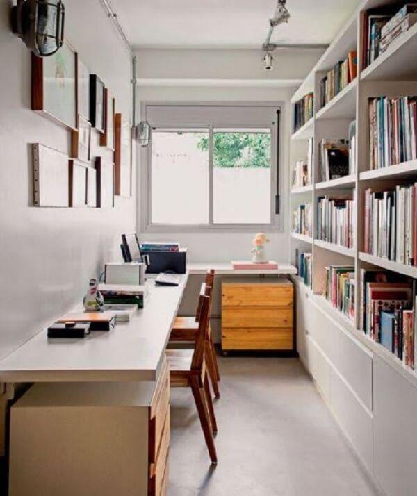 A estante embutida com diversas prateleiras auxilia na organização do escritório planejado