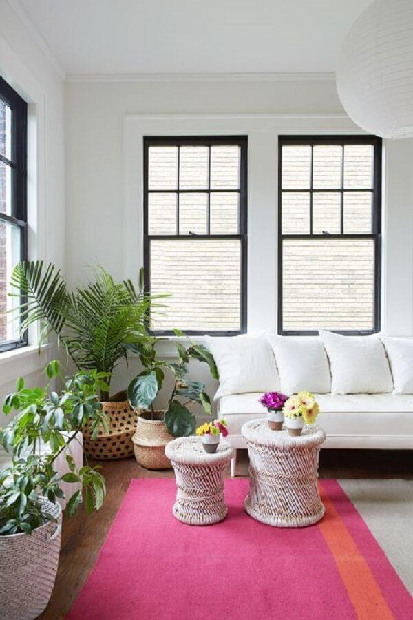 O tapete rosa se destaca no ambiente com sofá branco