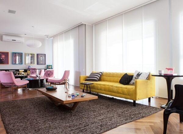 Ambiente descontraído com cadeiras em tom rosa e sofá amarelo