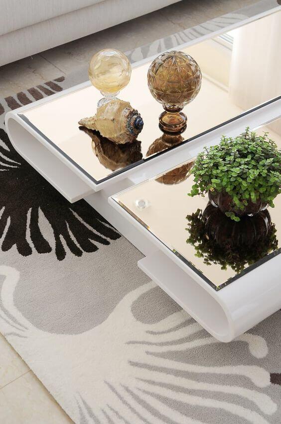 Mesa de centro espelhada e decorada com vasos e enfeites