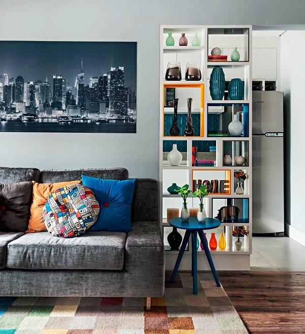 A estante nicho colorida separa o ambiente da sala de estar e cozinha