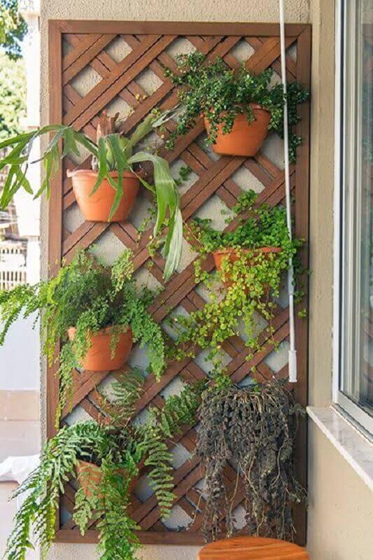 parede decorada com treliça de madeira com vasos Foto Artesanato do Céu
