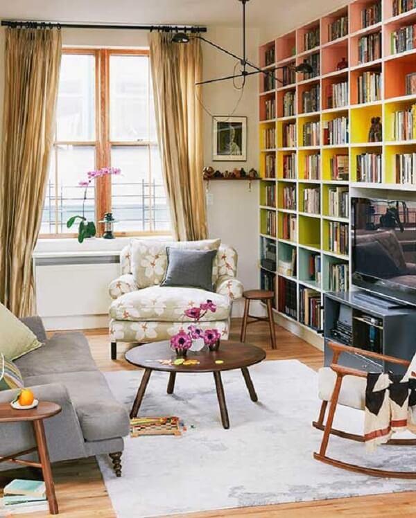 Sala de estar com estante nichos colorida acomoda diversos livros