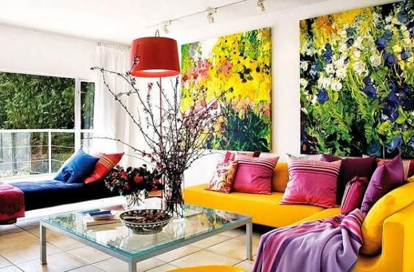 O sofá amarelo se harmoniza com os quadros decorativos do ambiente