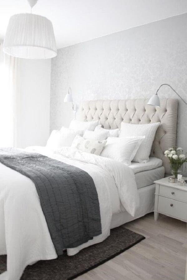 quarto branco decorado com cabeceira capitonê e papel de parede cinza claro Foto Sodimac