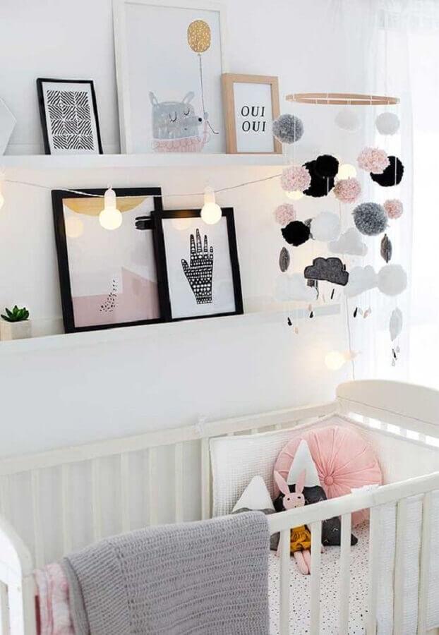quarto de bebê branco decorado com vários quadros apoiados em prateleira estreita Foto Pinosy