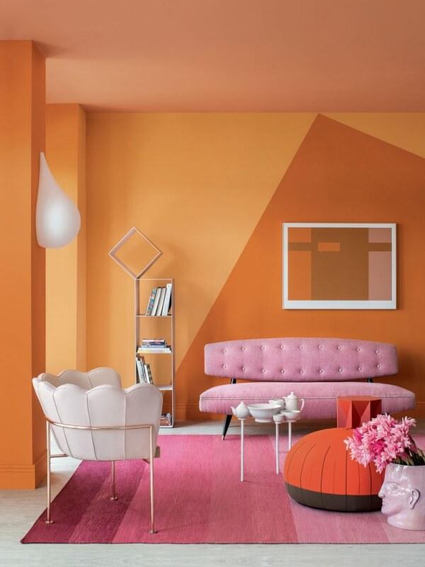 Sala de estar descontraída e alegra com parede laranja e tapete rosa