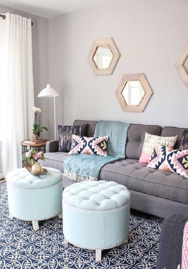 sala cinza decorada com puff capitonê redondo e várias almofadas Foto Overstock