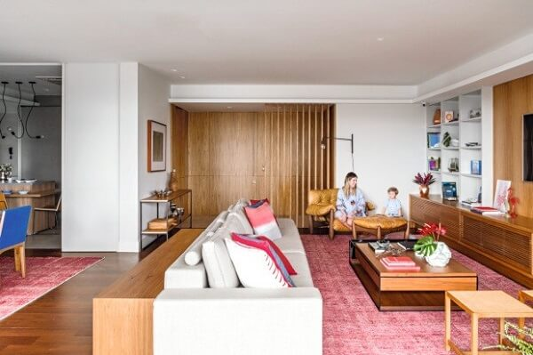 Integre ambientes usando o mesmo modelo de tapete rosa para sala de estar e sala de jantar