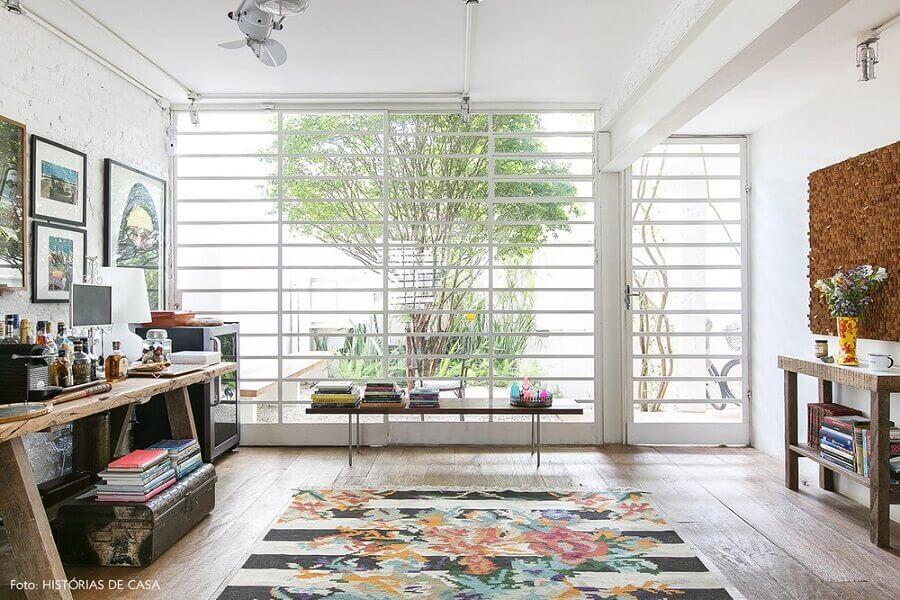 sala simples decorada com porta de ferro com vidro pintada de branco Foto Manual da Obra