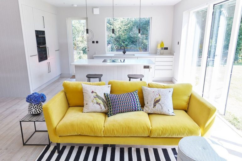 Sala com sofá amarelo e decoração clean