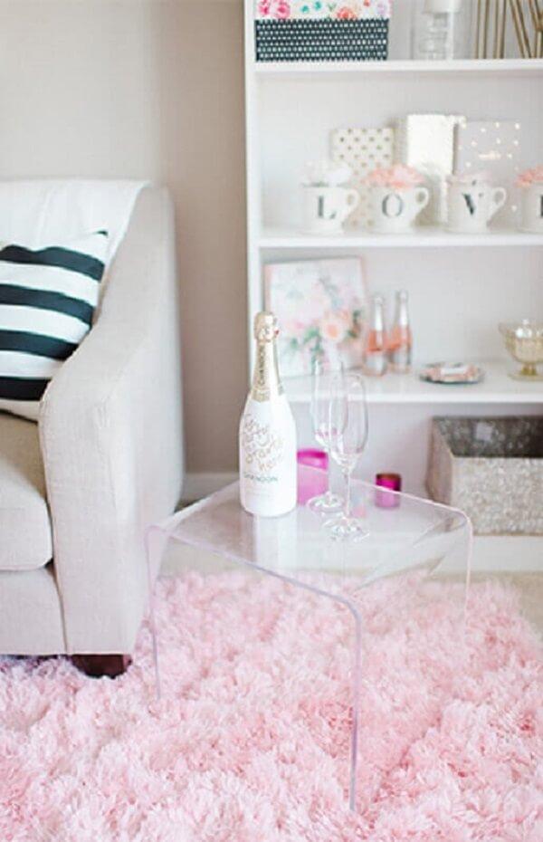 Sala com tapete rosa felpudo e mesa de acrílico