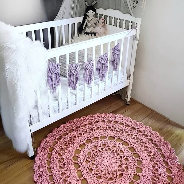 Quarto de bebê com berço branco e tapete rosa de crochê