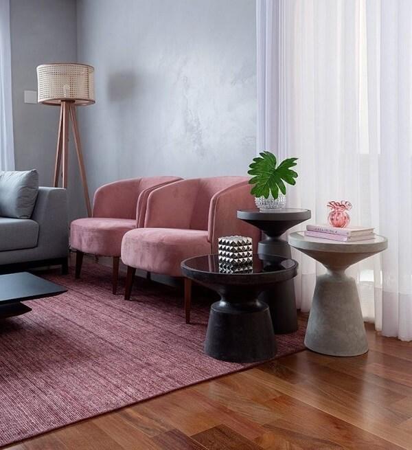 As poltronas do ambiente seguem a mesma tonalidade do tapete rosa