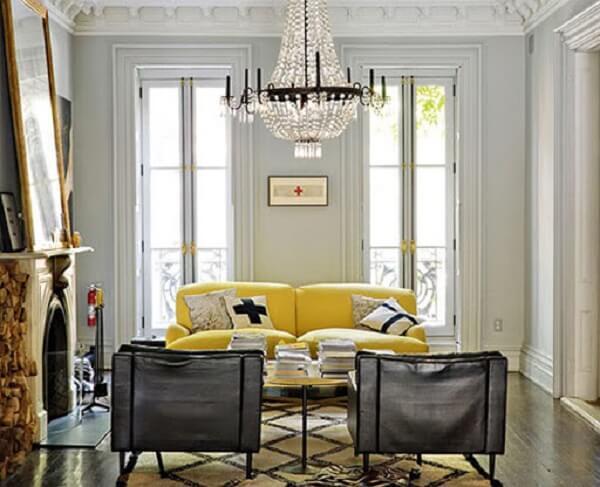Sala de estar com lustre de cristal e sofá amarelo