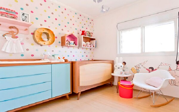 Quarto de bebê com nichos coloridos e papel de parede alegre