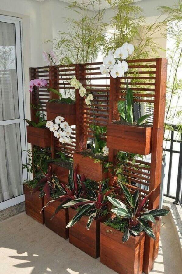 varanda decorada com treliça de madeira com vasos Foto Pinterest
