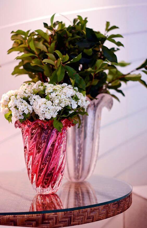 Vaso murano rosa com flores brancas e plantas