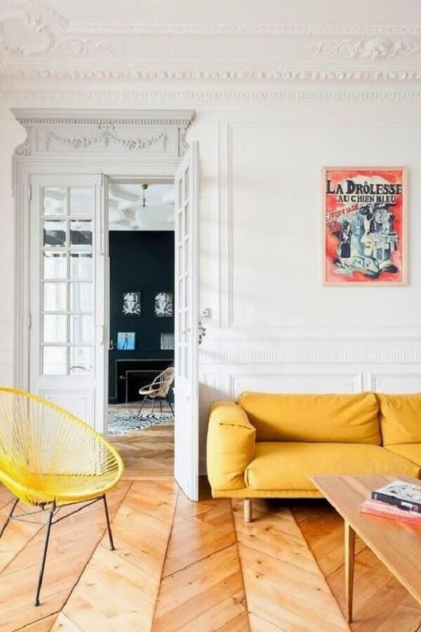 Sala com piso de madeira e sofá amarelo
