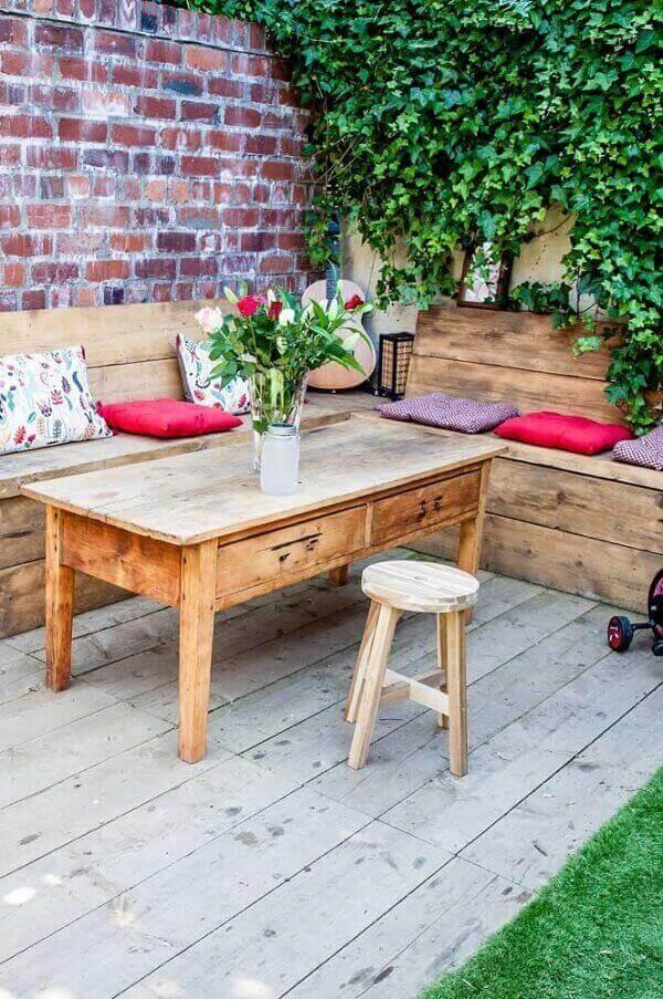 Área de lazer pequena com mesa e banco de pallet