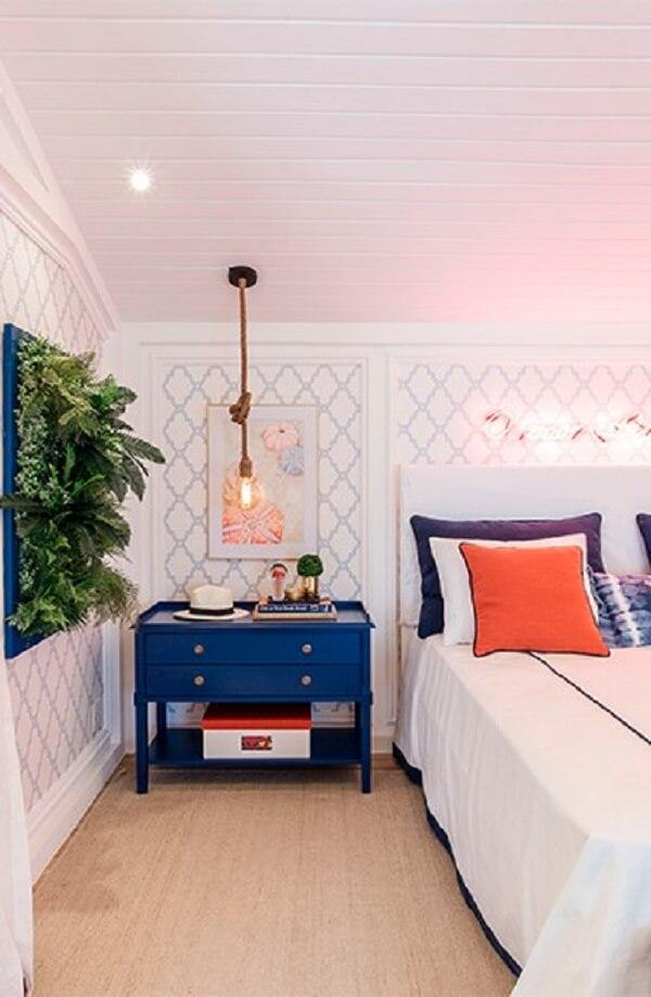 Móveis e objetos decorativos coloridos se destacam no quarto com parede branca
