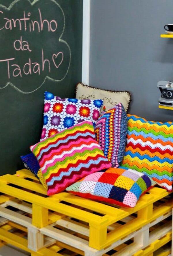 Banco de pallet com almofadas coloridas