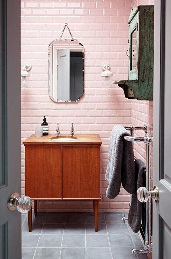 Banheiro com revestimento rosa e gabinete de madeira