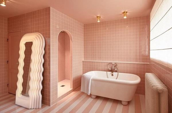 Banheiro rosa claro e branco com padrões de piso diferentes