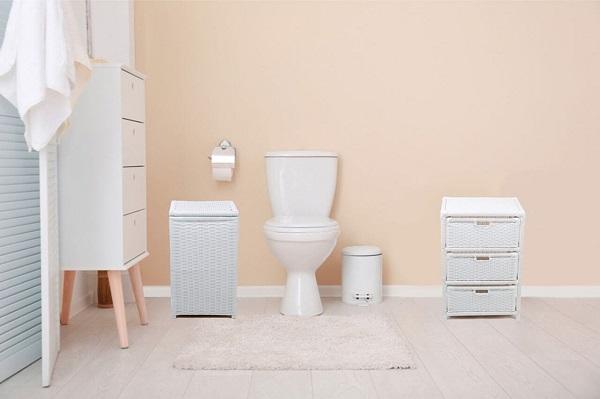 Banheiro rosa claro e cestos de palha branca