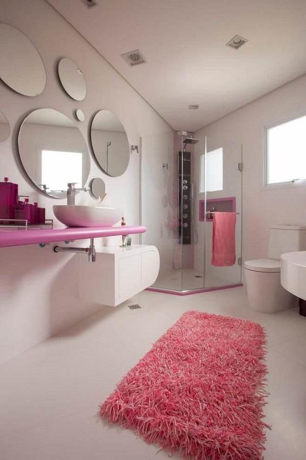 Banheiro rosa com bancada rosa e diversos espelhos redondos