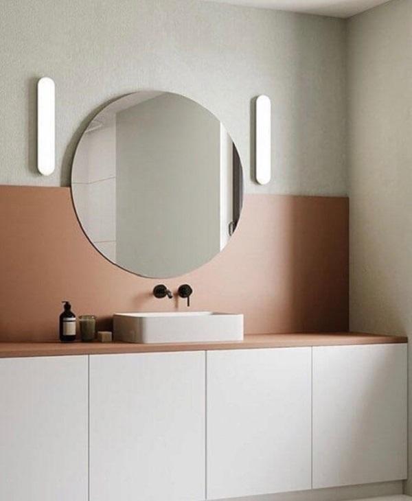 Banheiro rosa com espelho redondo sem moldura