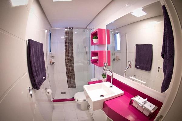 Banheiro rosa com nicho e gabinete rosa