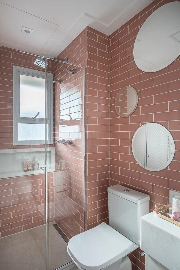 Banheiro rosa com revestimento e vaso e pia branco