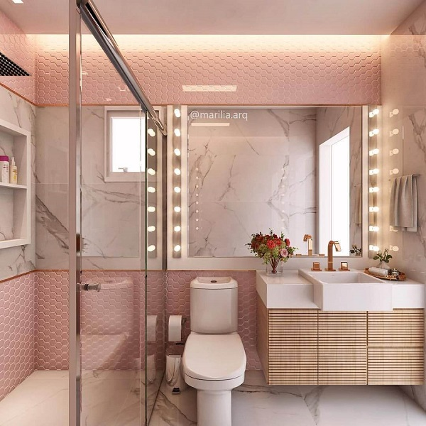 Banheiro rosa com revestimento rosa e espelho iluminado