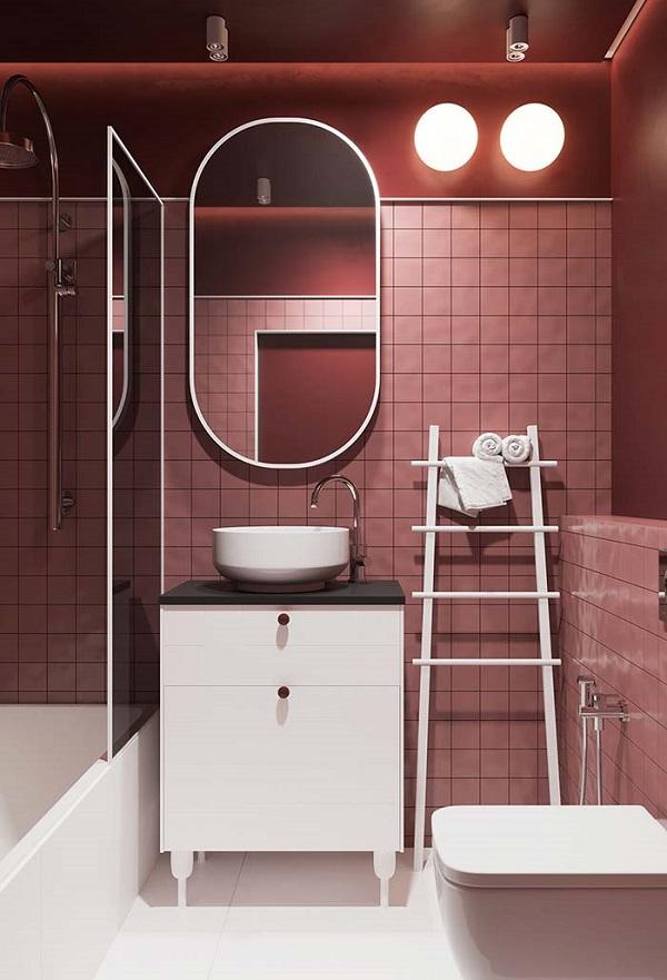 Banheiro rosa com revestimento e móveis branco