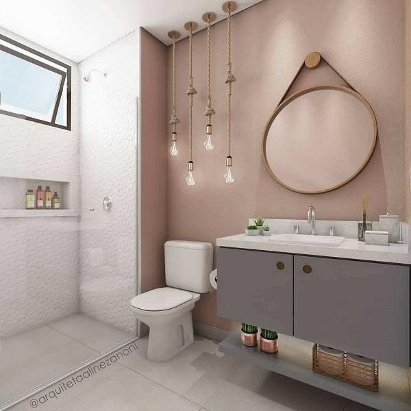 Banheiro rose gold com gabinete cinza espelho redondo e luminárias pendentes