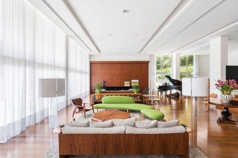 Decoração de sala ampla com chaise verde como ponto focal