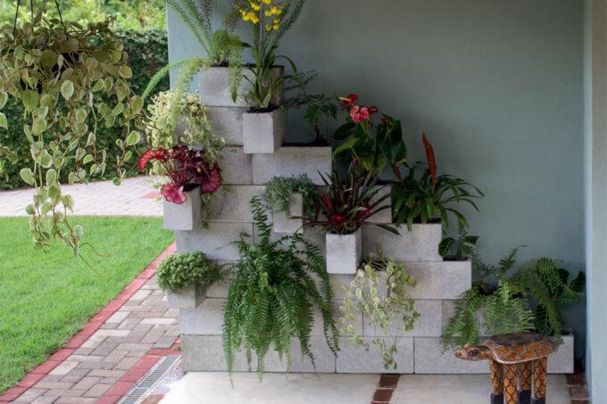 Parede verde, bloco de concretos alinhados como vasos e diferentes flores e plantas