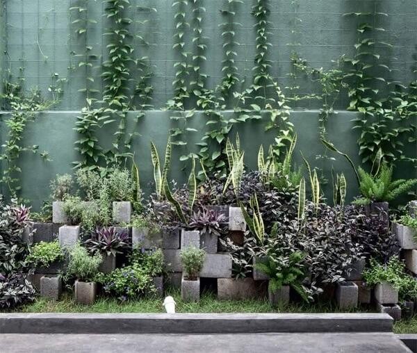 Parede de fundo verde, blocos de concreto sem pintura como vasos