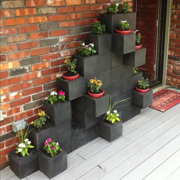 Parede de tijolos, blocos de concretos pintados de preto alinhados como vasos