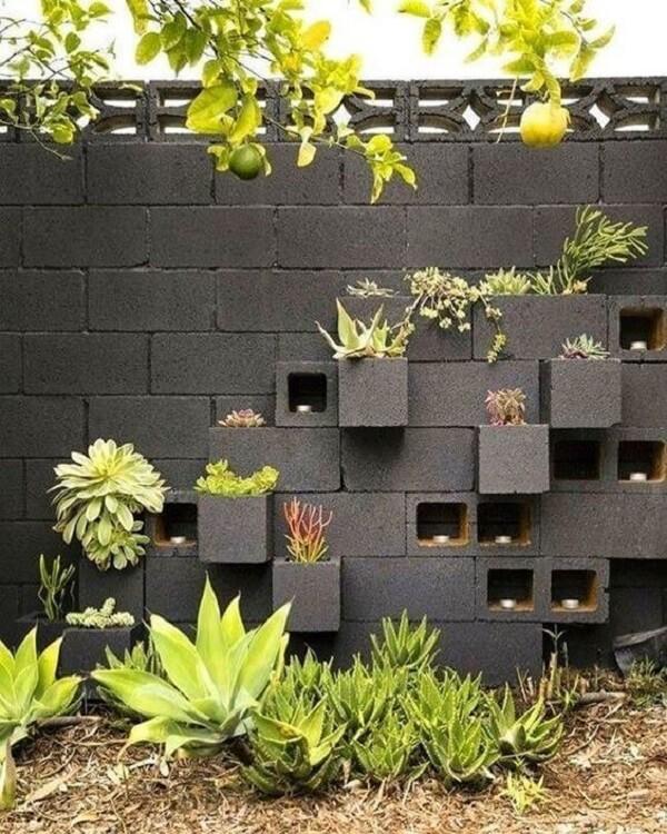 Parede e blocos de concreto pintados de preto como vasos