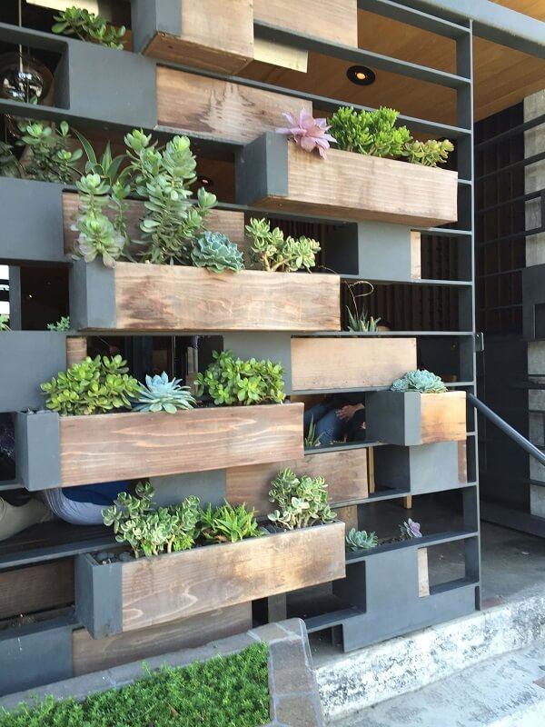 Canteiros de madeira suspensos em uma parede de ferro