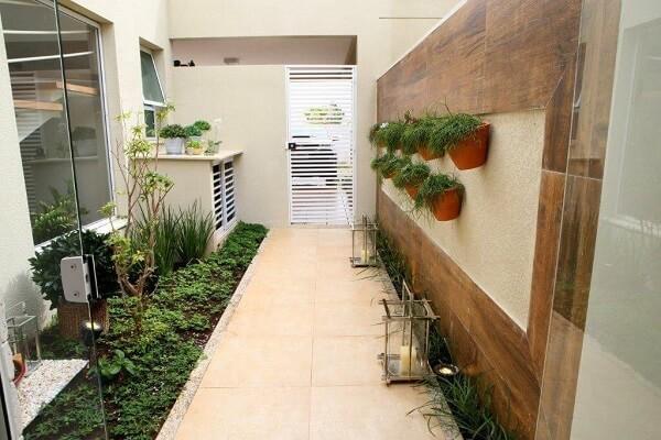 Canteiro com grama e plantas, parede clara com duas fileiras de vasos de cerâmica suspensos