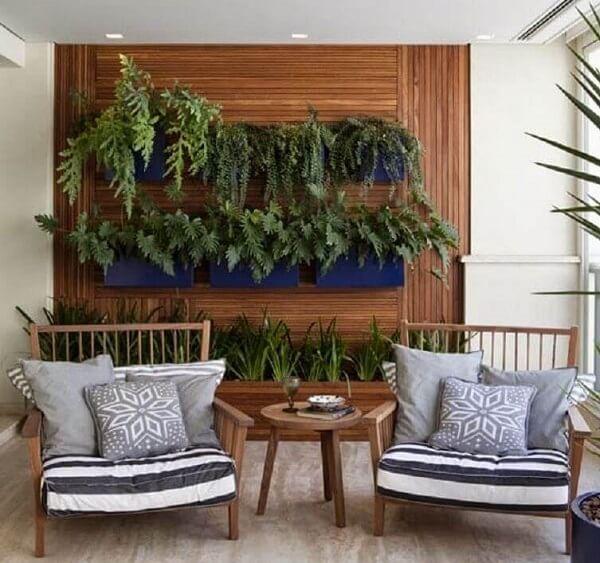 Parede de madeira com canteiros pretos suspensos, duas cadeiras de madeira com almofadas brancas e mesa baixa de madeira