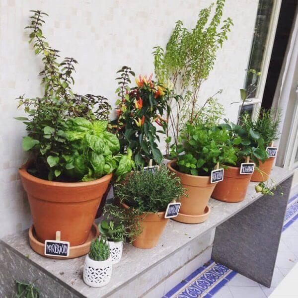 Vasos de cerâmica de diferentes tamanhos em um apoiador branco