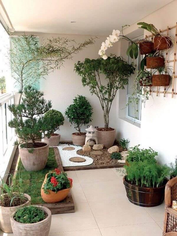Jardim de inverno com vasos de diferentes core e tamanhos, canteiro com grama e espaço demarcado com pedras decorativas