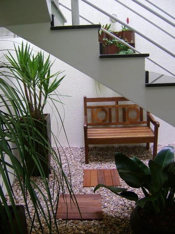 Jardim de inverno sob escada, banco de madeira de dois lugares, chão com pedras e vasos com plantas